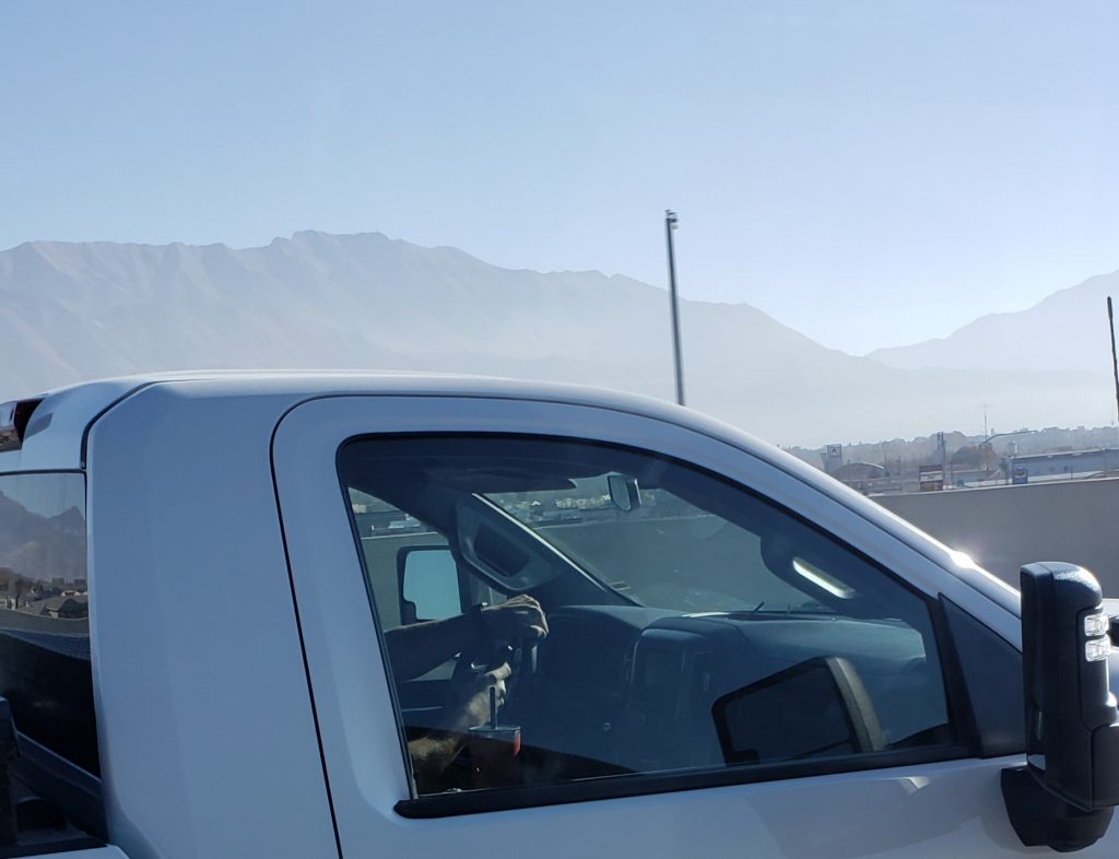 Image is taken from the unmarked van and shows a person holding a cell phone in one hand while driving on the freeway.