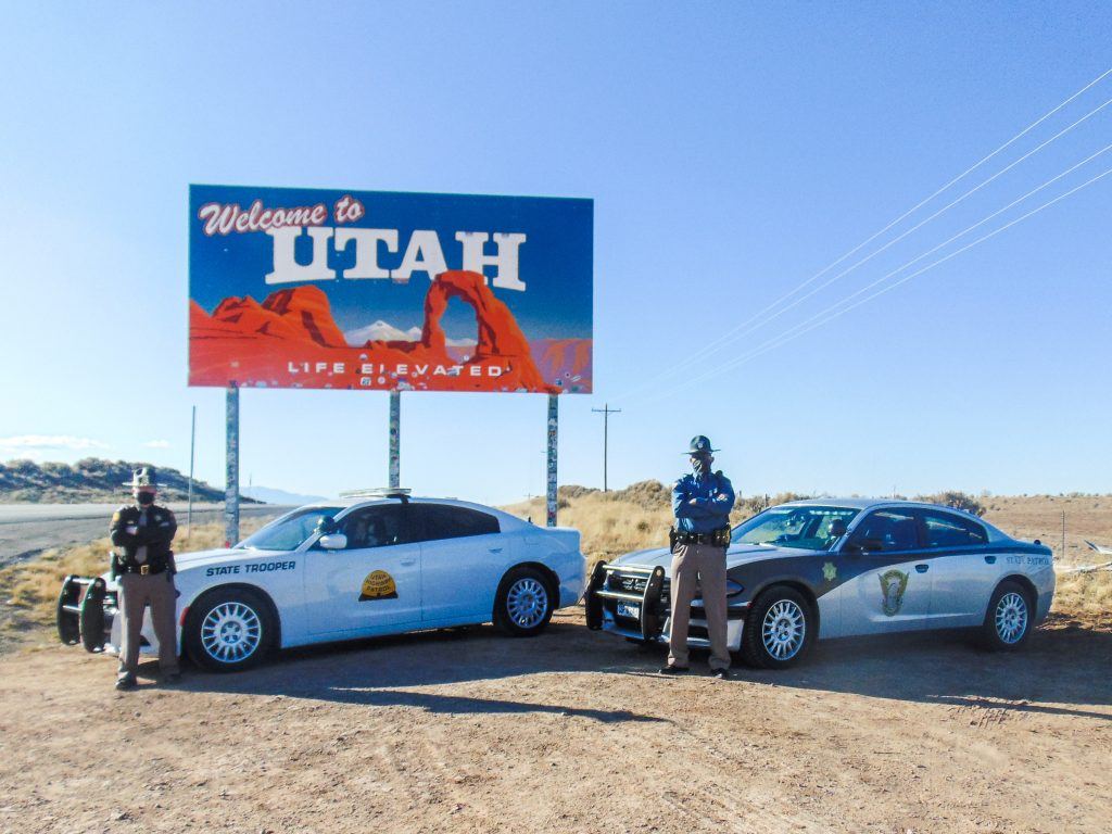 Image shows a UHP vehicle and an CSP vehicle parked in front of the welcome to Utah sign with a UHP Trooper and CO state Trooper standing in front of them.