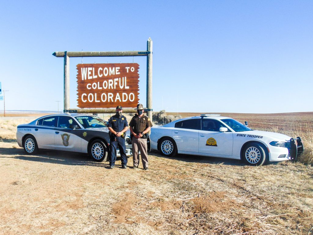 Image shows a UHP vehicle and an CSP vehicle parked in front of the welcome to Colorado sign with a UHP Trooper and CO state Trooper standing in front of them.