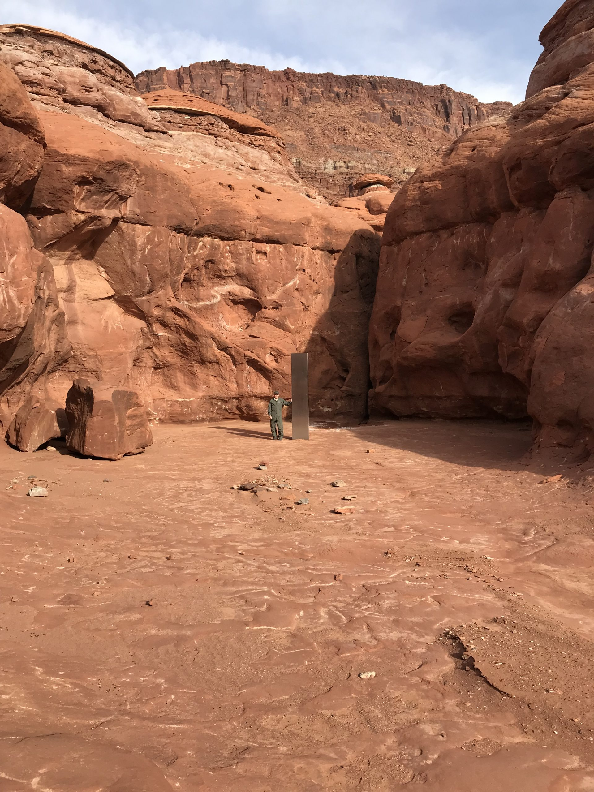 A crew member from the DPS Aero Bureau mission stands next to the metal monolith implanted in the ground in red rock.