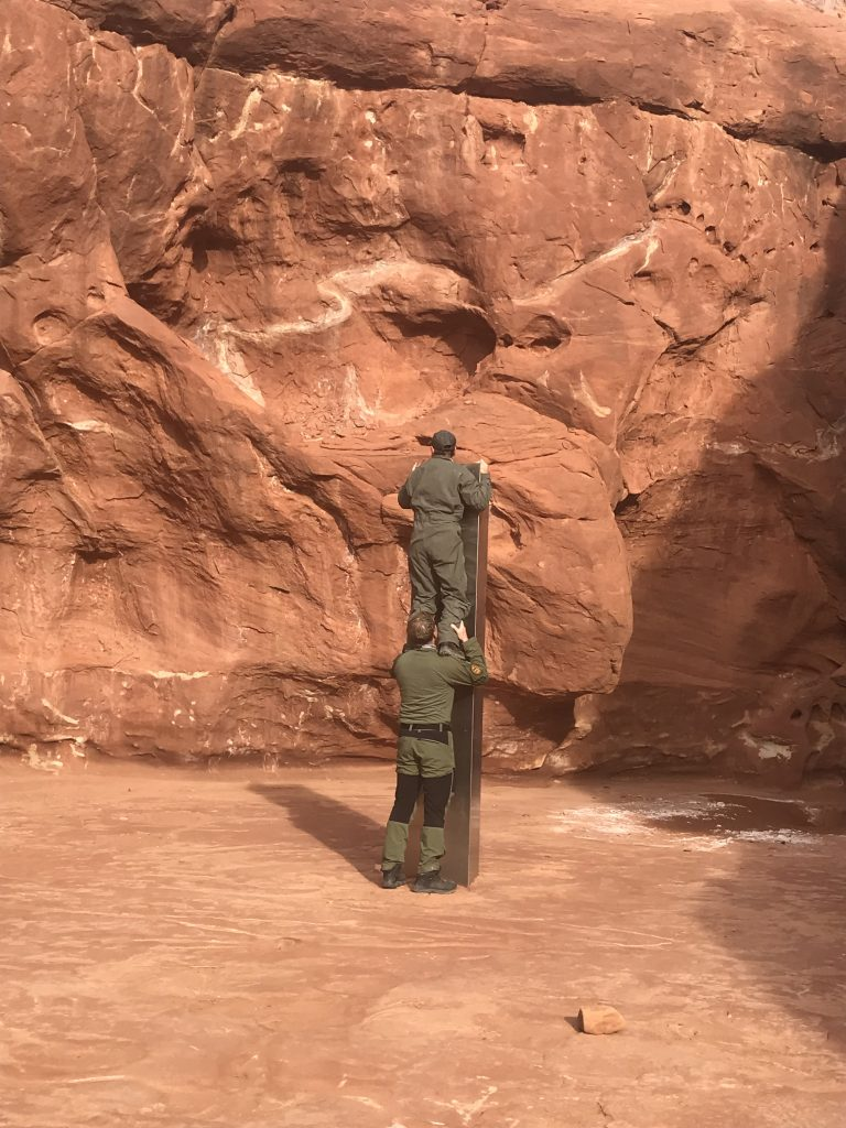 Two crew members - one standing on the other's shoulders - from the DPS Aero Bureau mission stands next to the metal monolith implanted in the ground in red rock.