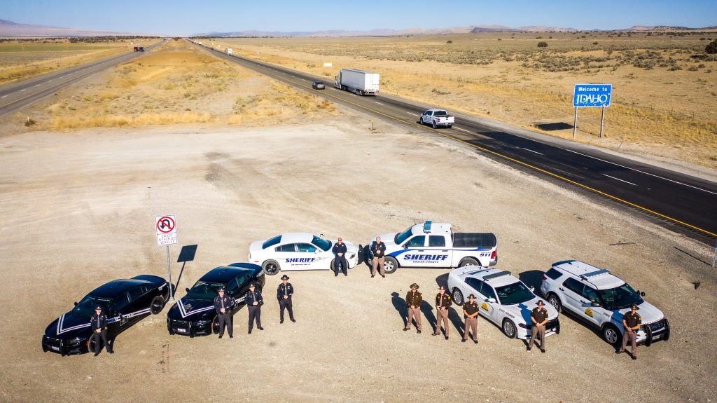 Image shows Idaho State Police Officers, UHP Troopers and Deputies from Cassia and Oneida County Sheriff's Office stand in front of their vehicles in the median of I 84 with the welcome to Idaho sign in the back.