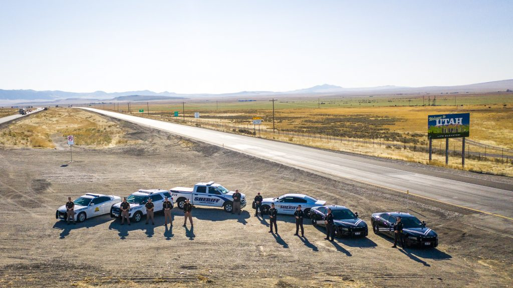 Image shows Idaho State Police Officers, UHP Troopers and Deputies from Cassia and Oneida County Sheriff's Office stand in front of their vehicles in the median of I 84 with the welcome to Utah sign in the back.