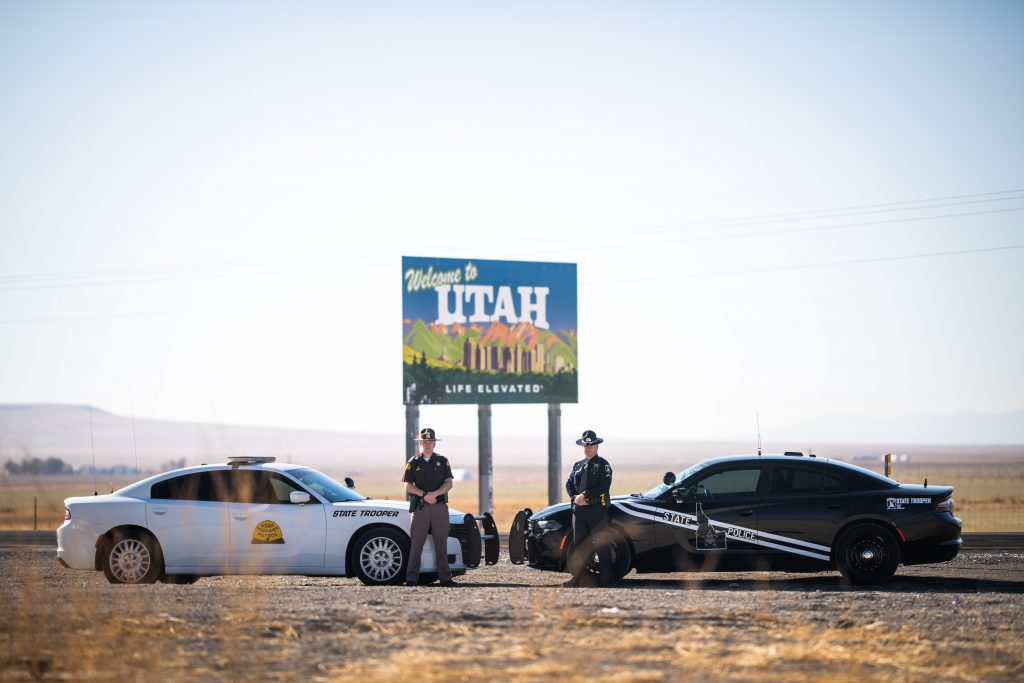 Image shows an Idaho State Police Officer and a UHP Trooper standing in front of the their vehicles which are in front of the Welcome to Utah sign.