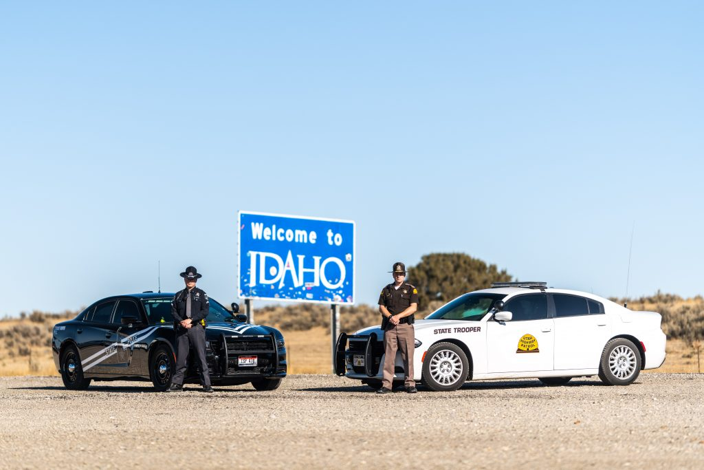 Image shows an Idaho State Police Officer and a UHP Trooper standing in front of the their vehicles which are in front of the Welcome to Idaho sign.