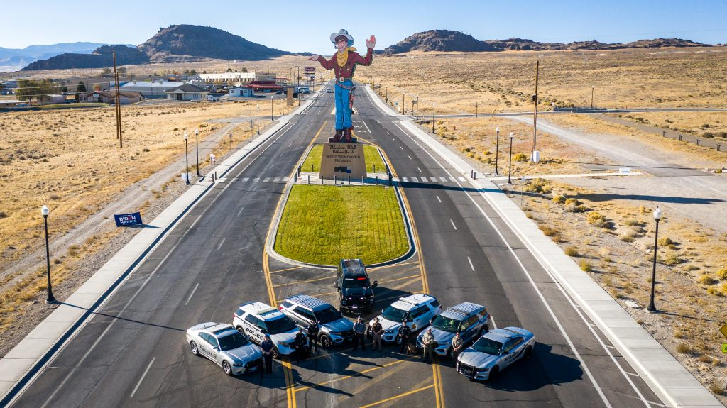 Image shows officers from Tooele County Sheriff's Office, Elko County Sheriff's Office, West Wendover PD, Wendover PD, UHP, NHP standing in front of their vehicles which are positioned in front of the Wendover Will sign.
