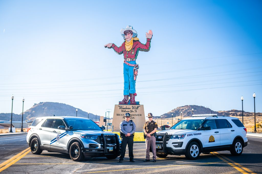 Image shows a NHP Trooper and UHP Trooper standing in front of their vehicles which are in front of the Wendover Will sign.