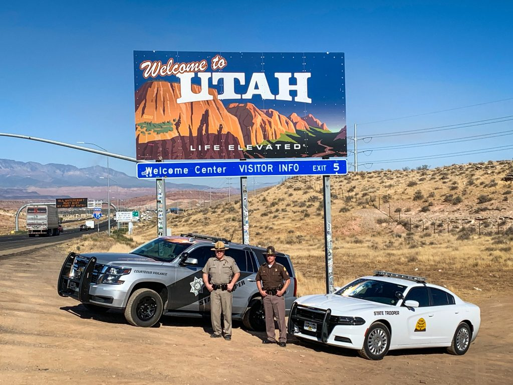 Image shows a UHP vehicle and an AZHP vehicle parked in front of the welcome to Utah sign with a UHP Trooper and AZ state Trooper standing in front of them.
