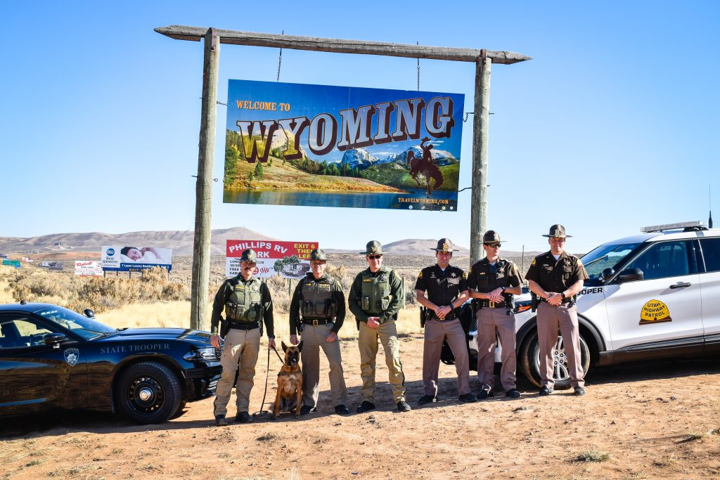 Image shows a group of Wyoming Highway Patrol Troopers and Utah Highway Patrol Troopers standing in front of their vehicles which are positioned in front of the Welcome to Wyoming sign.
