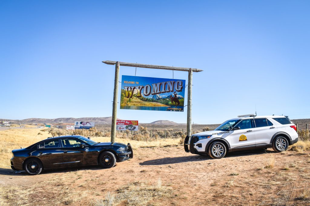Image shows a Wyoming Highway Patrol vehicle and a UHP vehicle which are positioned in front of the Welcome to Wyoming sign.