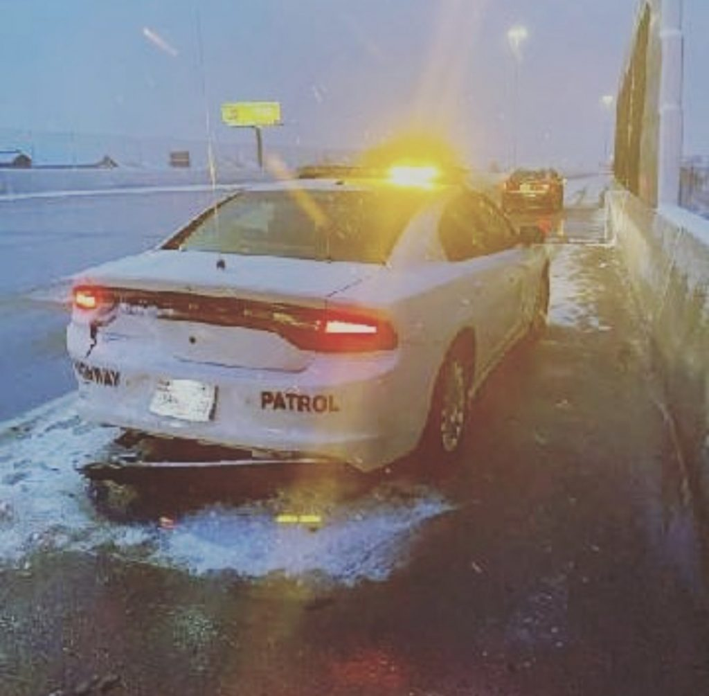 Image shows a UHP patrol car with damage to the left rear side after a car hit it on the shoulder.